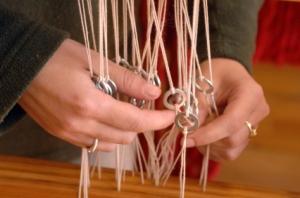 Frauenhände sortieren Kettfäden am Webstuhl